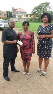Monday Ubani giving  Josephine Ugwu the cheque