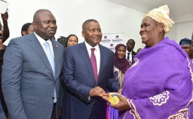 L-R: Lagos State Governor, Mr. Akinwunmi Ambode, with Chairman, Dangote Group, Alhaji Aliko Dangote and a beneficiary, Mrs. Idowu Agbenimadehin from Epe