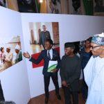 A Young Creative artist Bayo Omoboriowo explaining his works to President Muhammadu Buhari accompanied by the Vice President Prof Yemi Osinbajo on Photo exhibition tour