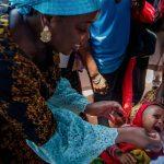 Mrs. Bindow deworming an infant