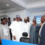 President Muhammadu Buhari listens as Minister of Transportation, Mr Rotimi Amaechi conducts him round the Campaign Office